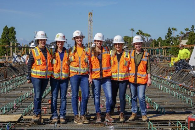 A group of female construction workers smile for the camera.