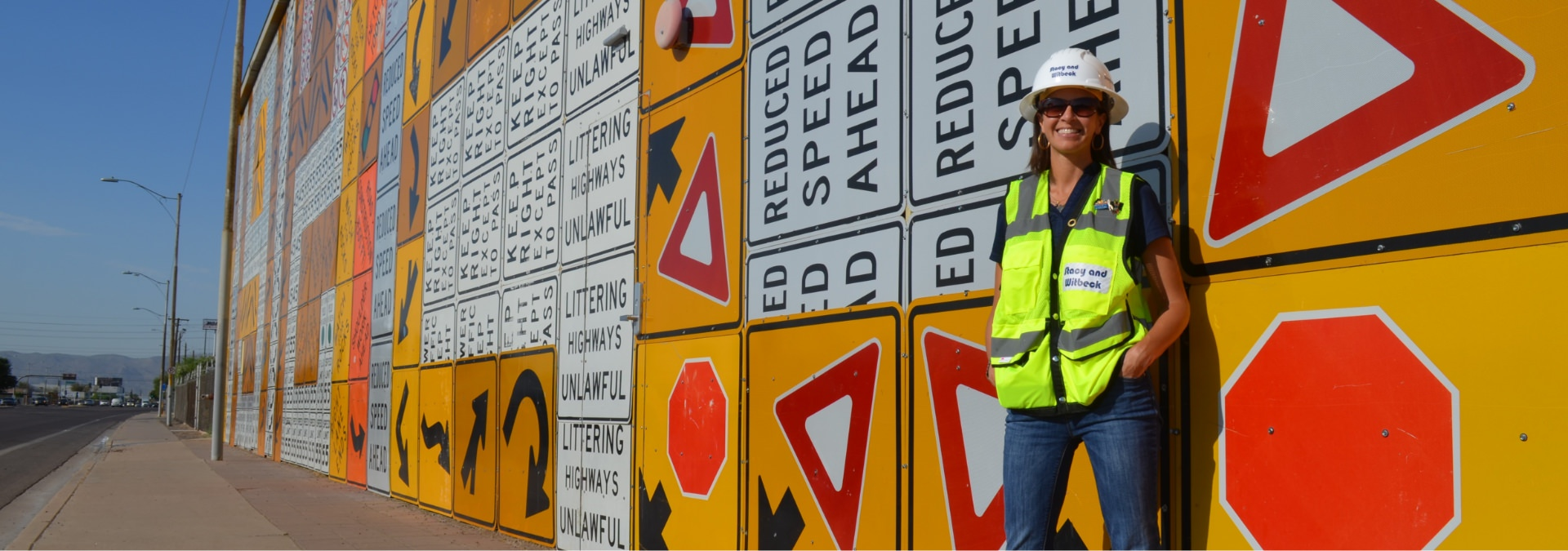 A woman leans against a wall covered in construction signs.