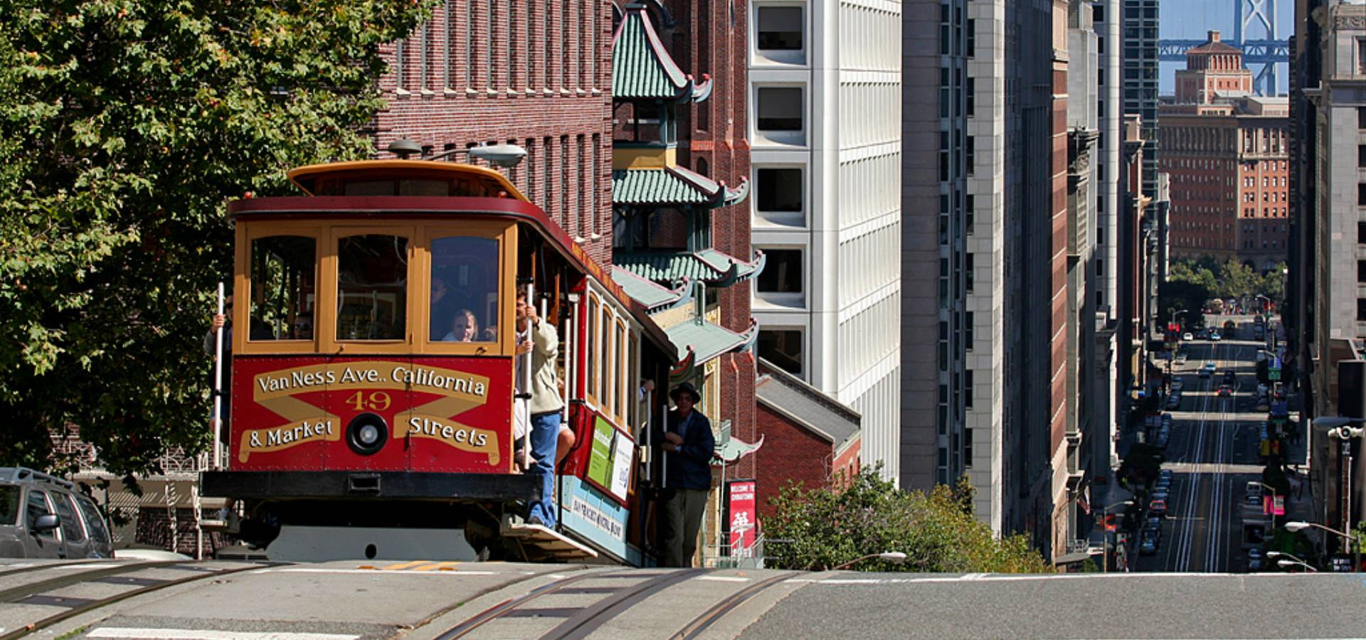 San Francisco street car comes up over a steep hill.